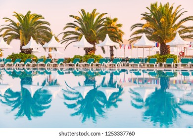 Hotel in Turkey with pool in foreground, white sun shade umbrellas, palms and chairs in background