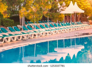 Hotel in Turkey with pool in foreground, white sun shade umbrellas and chairs in background