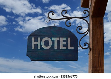 Hotel wooden vintage sign hanging over blue sky with clouds