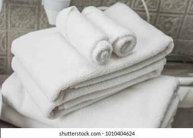 Hotel`s bedroom. White fluffy, rolled towels.Close up view