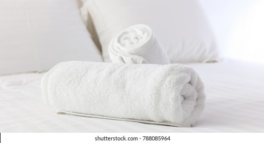 Hotel's bedroom. White fluffy, rolled towels, linen sheets and pillows on a tidy bed. Close up view.