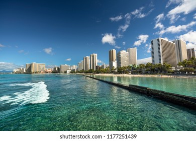 Hotels and tourists vacation on Waikiki Beach shore by the Pacific Ocean in Honolulu Oahu Hawaii USA