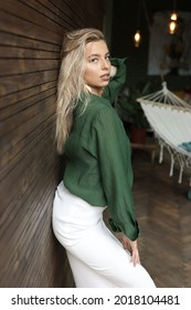 hoto of a beautiful girl in full growth standing on a background of a wooden wall. She is wearing a long white skirt and a green shirt