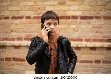 hoto of teenage boy aged 11-12 is talking on smartphone against background of brick wall in city