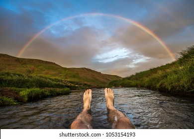 Hotspring bath and rainbow, Reykjadalur valley, Iceland