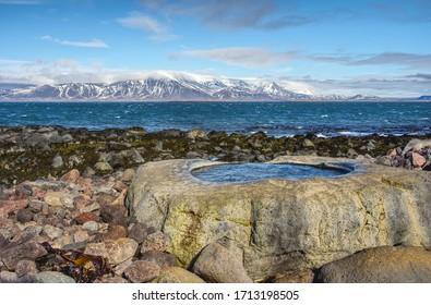 Hot-water stone bath located on the Atlantic. Photo taken at low tide. Low tide discovered seaweed growing on the seabed. Snow-capped mountains and the ocean are also visible in the photo.