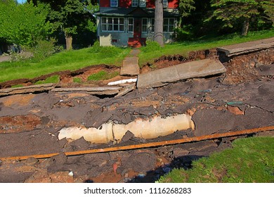 HOUGHTON, MICHIGAN - JUNE 18 2018: Intense storm rainfall and flash flooding in June of 2018 caused damage to yards and exposed underground pipelines on Agate Street in the town of Houghton, Michigan.