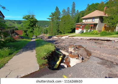 HOUGHTON, MICHIGAN - JUNE 18 2018: Intense storm rainfall and flash flooding in June of 2018 exposed numerous sinkholes and washed out Agate Street in the town of Houghton, Michigan.