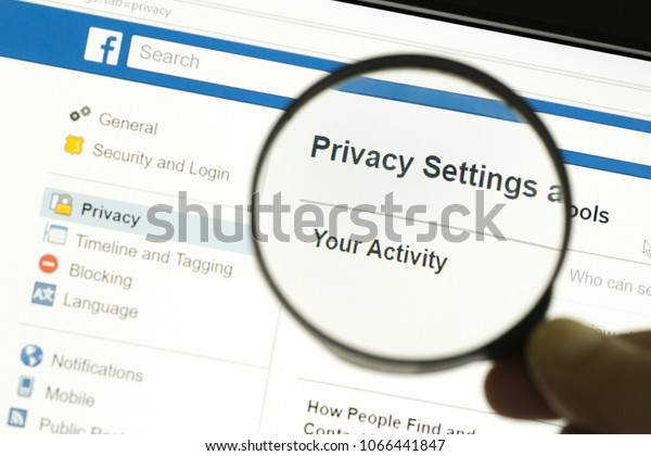 """Houilles, France - April 10, 2018:Hand holding a magnifying glass and magnifying the word """"Privacy settings"""" located on the privacy page of the facebook site."""