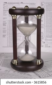 An hour glass rests on tax forms. More tax forms serve as the background.