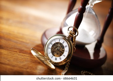 Hour glass or sand timer with vintage pocket watch, symbols of time with copy space