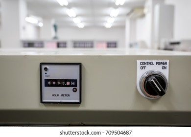 Hour meter and control power with industrial room background.