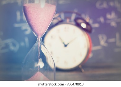 Hourglass against on wooden surface with a blackboard background