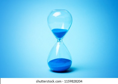 Hourglass with blue sand on blue background