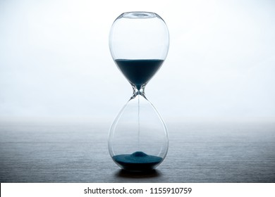 hourglass with blue sand on a white background and a gray table close up