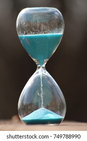 An hourglass with blue sand selective focus