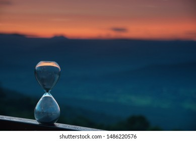 An hourglass with blur forest in twilight time at a morning