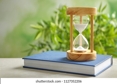 Hourglass and book on table against blurred background. Time management