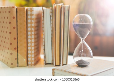 hourglass with books on wooden table