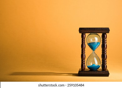 Hourglass clock on yellow vintage background