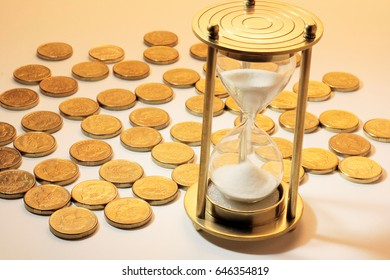 Hourglass and Coins on Warm Background