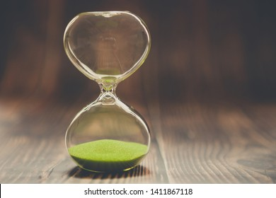 Hourglass as a concept of past time, lost time or completed cases. Clock on wooden background.
