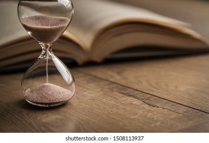 Hourglass countdown with a book. Hourglass and open bible symbolizing the end times. Time is running out.