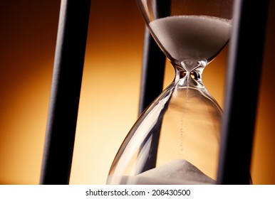 Hourglass counting down the time with sand running through the glass bulbs, close up view on a golden background