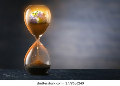 Hourglass with crumbling Earth on dark background. Concept of time