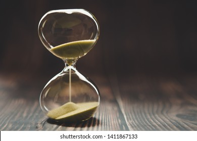 Hourglass with falling sand inside a glass bulb, passing time or lost time on a dark background with space for text