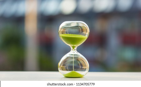 Hourglass with green sand on a blurred background