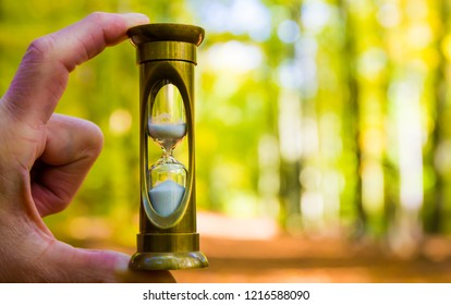 an hourglass in the hand of a man symbolizes the passage of time