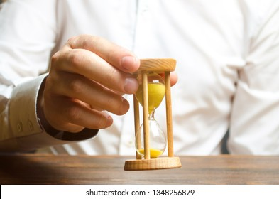 Hourglass in the hands of a person in a white shirt. Business management. Time management Increase efficiency, reduce costs and bureaucracy. Logistics, process simplification, savings.