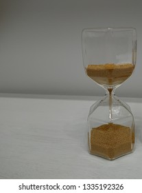 hourglass isolated. sandglass on white wooden table with copy space. time is money concept.