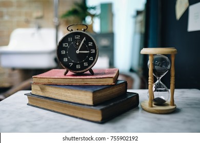 Hourglass and old clock in vintage style with old books, Antique Sand Clock, Read education concept