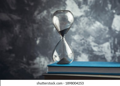 hourglass on the books on grey background