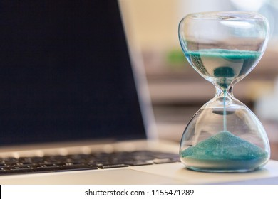 Hourglass on laptop computer with a pile of books. Concept for time management and countdown to deadline