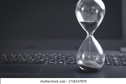Hourglass on laptop keyboard. Time. Business