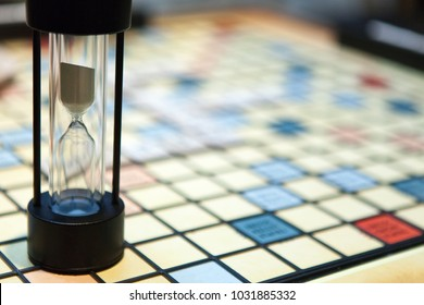 Hourglass on top of a crossword board with blur background. Sports and leisure. Countdown for game, competition.