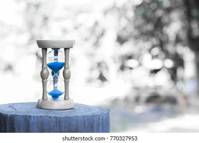 Hourglass on wood in the morning, natural blurred background