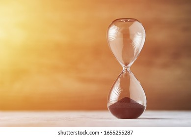 Hourglass on wooden background with copy space. Concept of running out of time and deadline