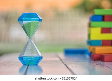 Hourglass on the wooden table with colorful wooden block as a background and copy-space