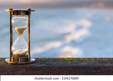 Hourglass Outdoors - sunlit hourglass or sand timer with a background of flowing water.