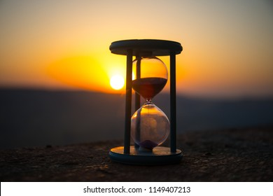 Hourglass Passing of Time Lapse Clouds. An hourglass in front of a bright blue sky with puffy white clouds passing. Time concept. Sunset time. Selective focus