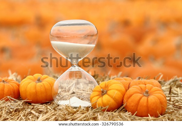 Hourglass and pumpkins in pumpkin patch. Holiday season countdown. Holiday-themed image.