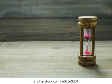 Hourglass Red clock with brown wood background