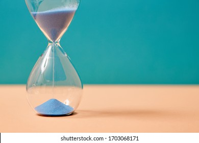 Hourglass with sand running through bulbs. Passing time. Business deadline. Time-limit. Productivity and optimization