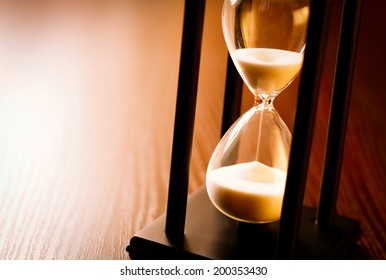 Hourglass with the sand running through in a wood frame on a wooden surface with shine and copyspace