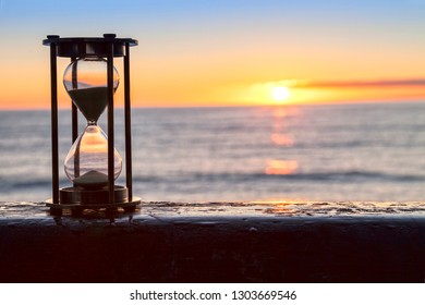 Hourglass or sand timer in front of a beatiful clear sunrise or sunset.