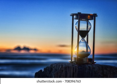Hourglass or sand timer in front of a beautiful clear sunrise or sunset.